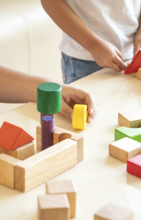 kids playing wooden block toy in their home, happy family concept